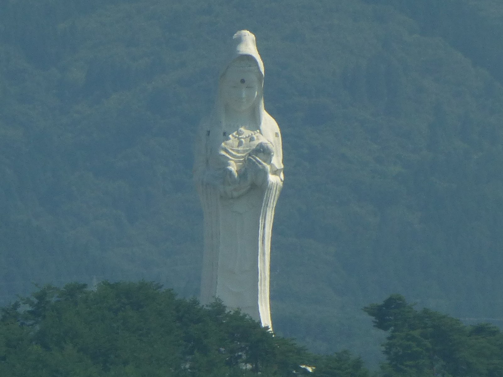 A white statue of a standing kannon.