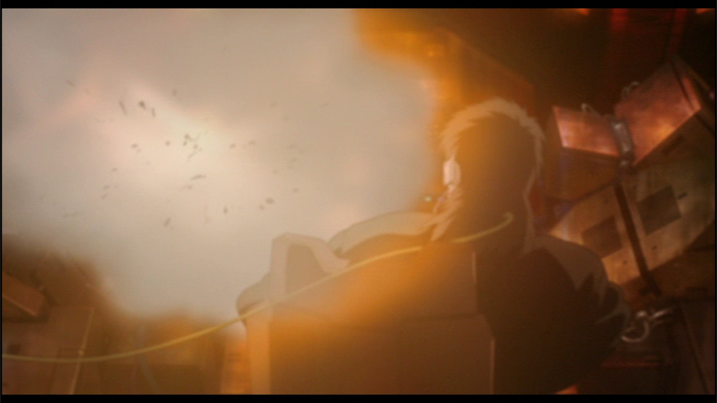 A person seated in an office chair, seen from the back, with some kind of VR headset on. In front of him an explosion, he is being thrown back by the force.