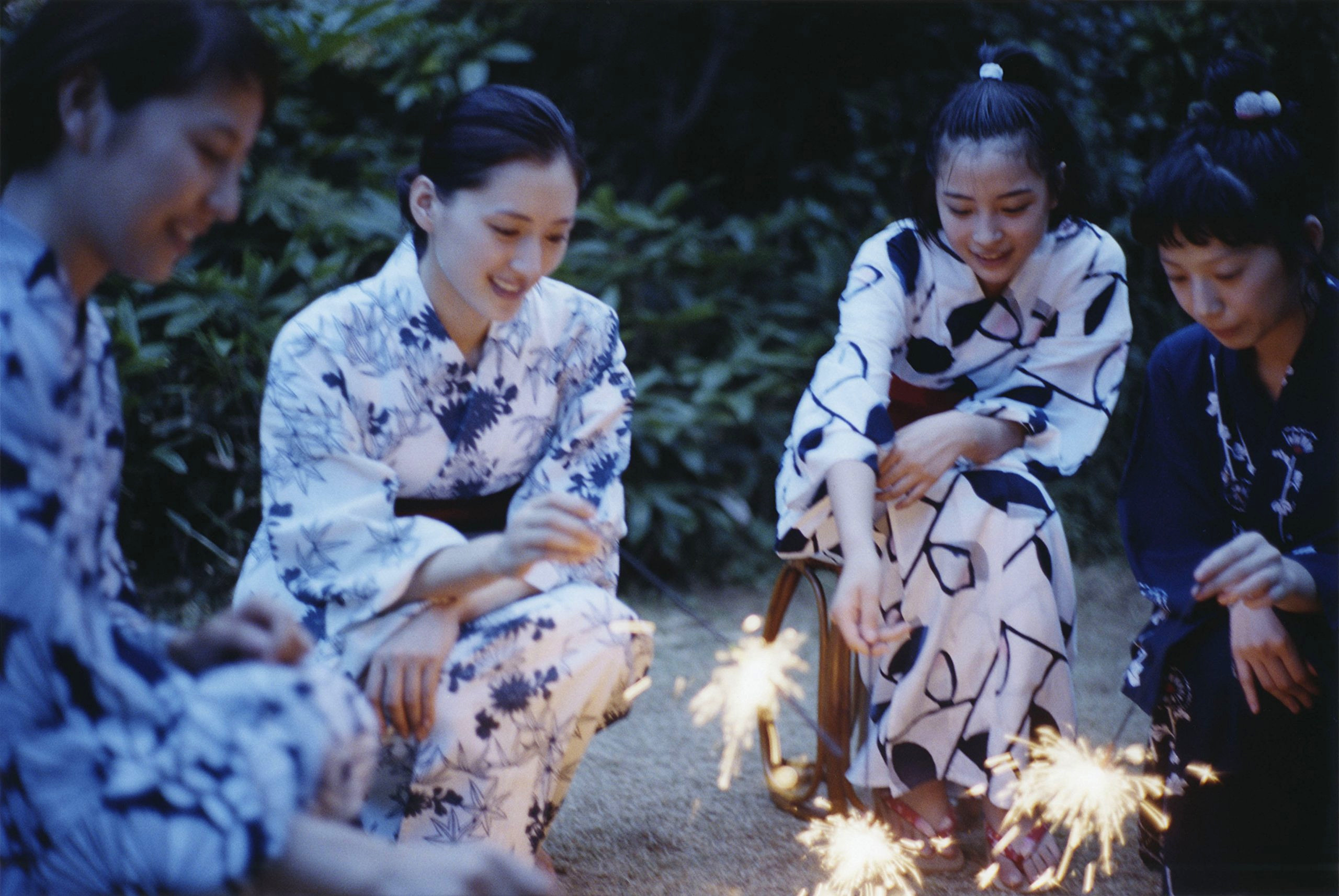 Four young women in yukata, holding sparklers.