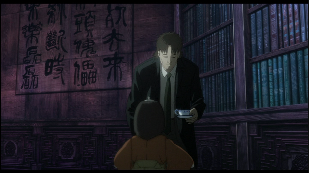The same space, a similar angle. The person in the suit is now closer, centre-screen, carrying a white china tea cup.